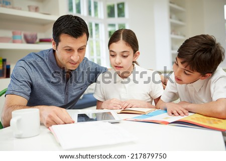 Father Helping Children With Homework Using Digital Tablet - stock photo