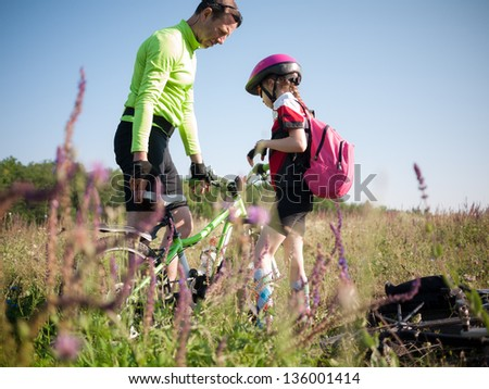 father helping daughter with her bicycle - stock photo