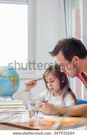 Father Helping Daughter With Homework - stock photo