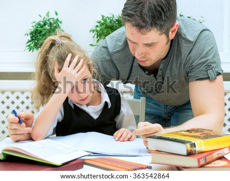 Father helping daughter with homework at home. - stock photo