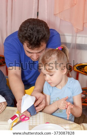 father helping his daughter to make paper crafts - stock photo