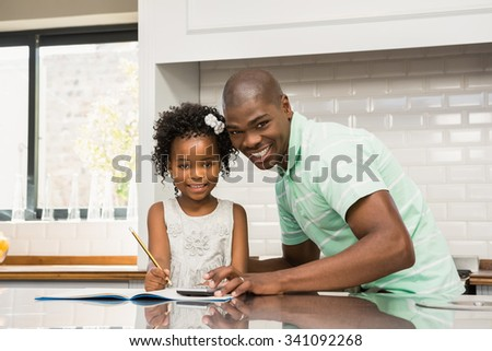 Father helping his daughter with homework in the kitchen