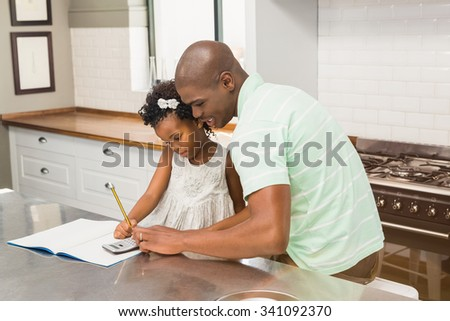 Father helping his daughter with homework in the kitchen - stock photo