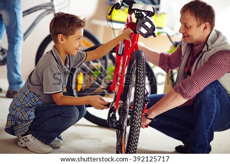Father helping his son fix a bicycle