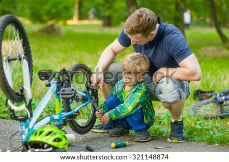father helping his son fix bicycle - stock photo