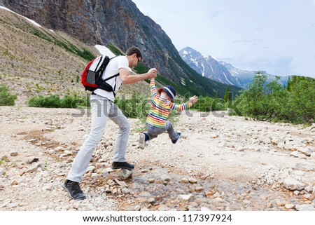 father helping his son to jump over stream in jasper national park - stock photo