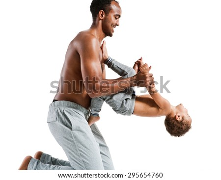 Father helping his son with his fitness exercises / photo set of sporty muscular Hispanic shirtless fitness man with his son over white background - stock photo