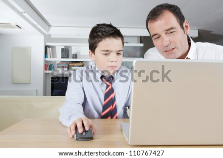 Father helping his son with his homework while sharing a laptop pc computer at home.