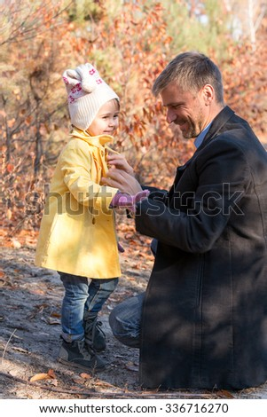 Father Helping Little Baby Daughter to Wear Coat on Walk in Autumnal Park  - stock photo