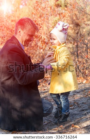 Father Helping Little Baby Daughter to Wear Coat on Walk in Autumnal Park Sun Shining Background - stock photo