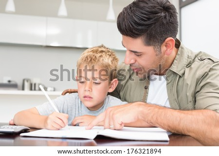 Father helping son with his math homework at home in kitchen - stock photo
