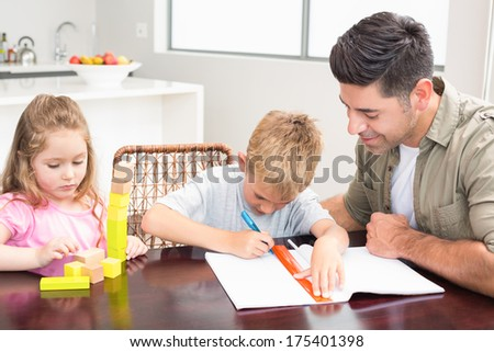 Father helping son with homework with little girl playing with blocks at home in kitchen - stock photo