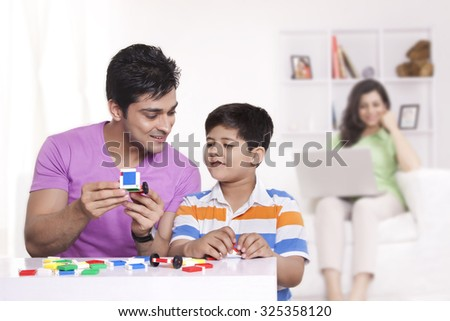 Father helping son with toys - stock photo