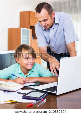 Father helping teenage son to do homework at the home