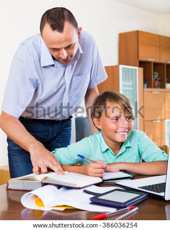 Father helping teenage son to do homework in home