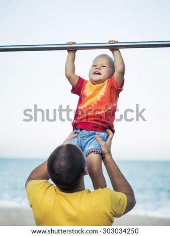 Father helps baby hanging on a pull-up bar - stock photo