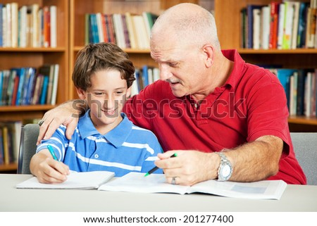 Father helps his son study for school at the library.   - stock photo