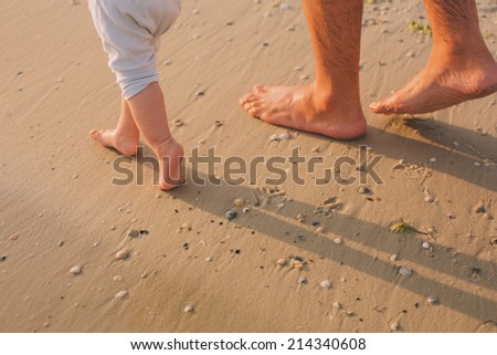 father helps to make the child's first steps on the beach - stock photo