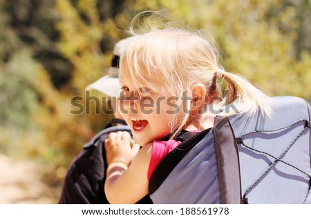 Father hiking with kid on backpack - stock photo