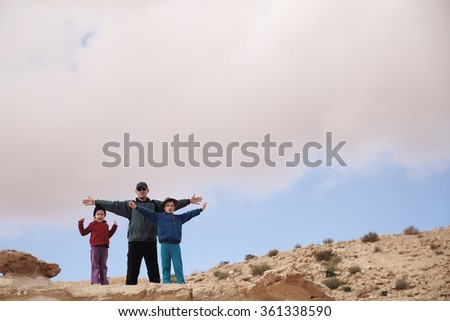 father hiking with two kids - stock photo