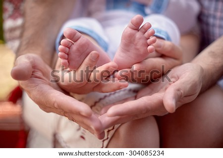 father hold the the feet of his new born son. - stock photo