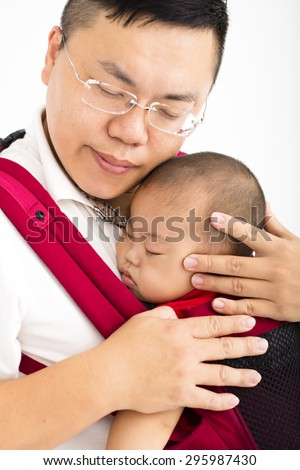 father  holding a baby in a baby carrier - stock photo