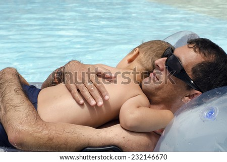 Father holding and hugging a small child relaxing in a swimming pool on a inflatable mattress.  - stock photo