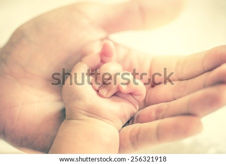 father holding baby hand in vintage filtered style - stock photo