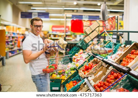 Father holding baby son in her arms and Shop supermarket.father and his cheerful son choosing fruits at the market. fruits and vegetables in the supermarket