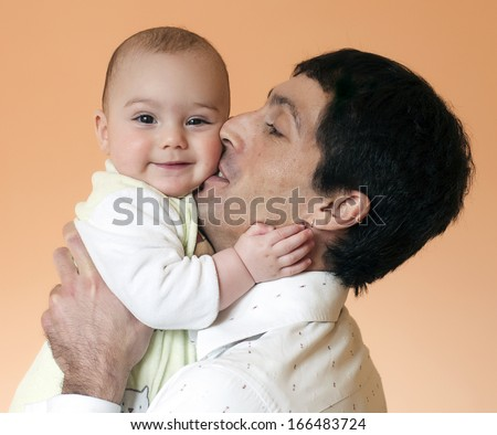 Father holding, cuddling and kissing a baby, happy parent and child concept.  - stock photo
