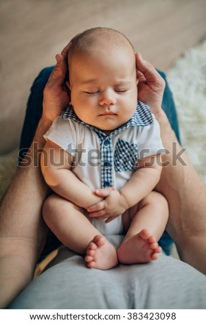 Father holding head of his newborn son in hands. Loving father hand holding cute sleeping newborn baby child - stock photo