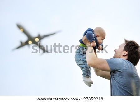 Father holding his baby (airplane on background) - stock photo