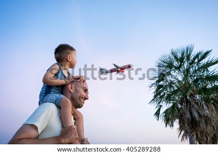 Father holding his little son on the shoulders when airplane flying in the sky - stock photo