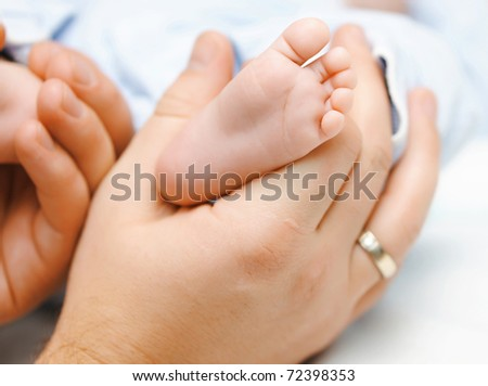 Father holding his newbon baby's feet - stock photo