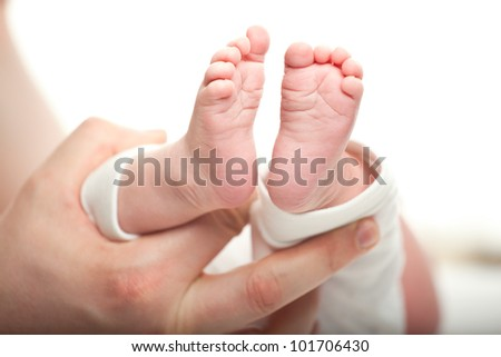 Father holding his newborn baby's feet, closeup shot, shallow dof - stock photo