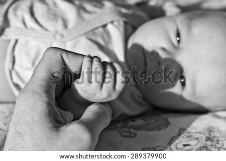 Father holding his newborn son hand. Black and white image with blurred background - stock photo