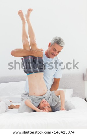 Father holding his son upside down having fun at home in bedroom - stock photo