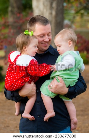 Father holding his twin babies outdoor at park - stock photo
