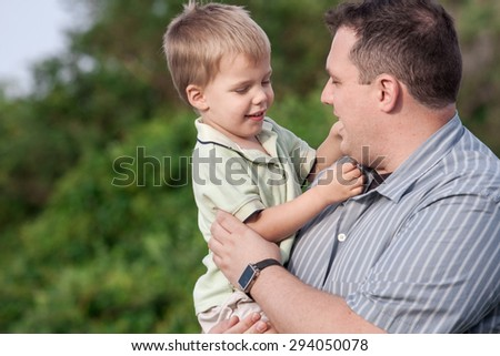father holding his 2 year old son outdoors - stock photo