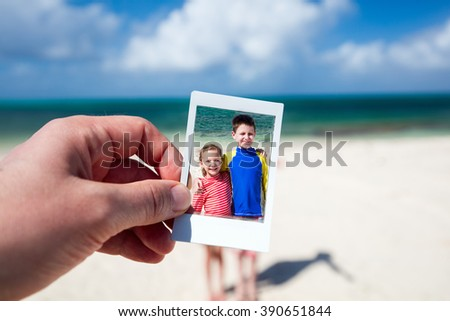 Father holding instant photo of his kids at tropical beach during Caribbean summer vacation - stock photo
