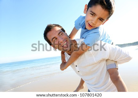 Father holding son on his shoulders at the beach - stock photo