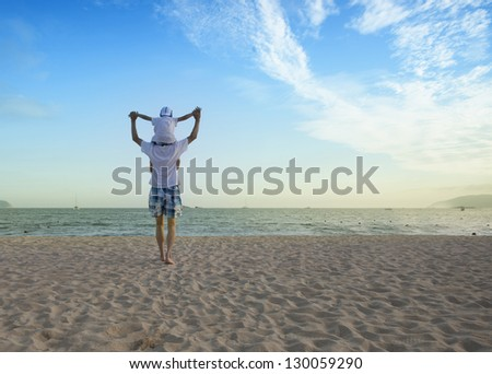 Father holding son on his shoulders at the beach with blue sky - stock photo