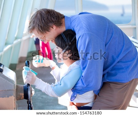 Father holding up disabled son, helping him to play with steering wheel on ferry boat deck. - stock photo