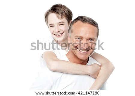 Father holding young son who has his arms around his neck - stock photo