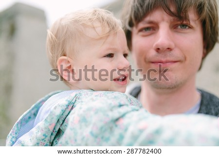 Father holds a cute crying baby on his hands - stock photo