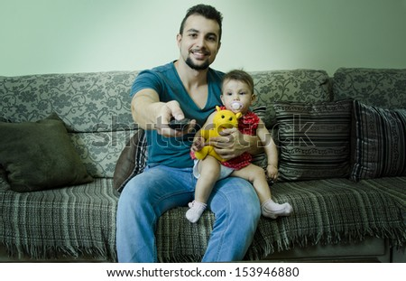 Father holds baby with pacifier and watching tv with remote control.