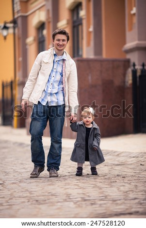 Father holds daughter's hand on the street.They both stand on the street with stone paving.Girl is dressed on grey coat and dress with white flower in hair. Young man dressed on white jacket and jeans - stock photo