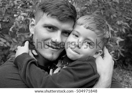 father holds his son in his arms, outdoors