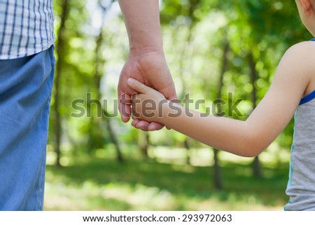 Father holds the hand of a little child in sunny park outdoor, united family concept, nature background, shallow dof