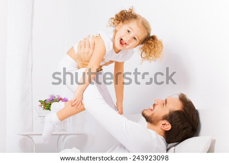 Father holds with arms his laughing daughter - stock photo
